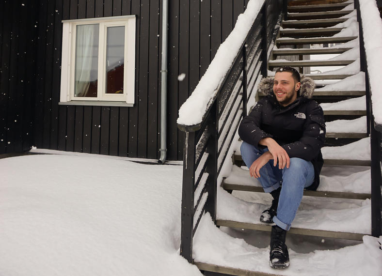 International exchange student in front of Storhove student dormitory during winter