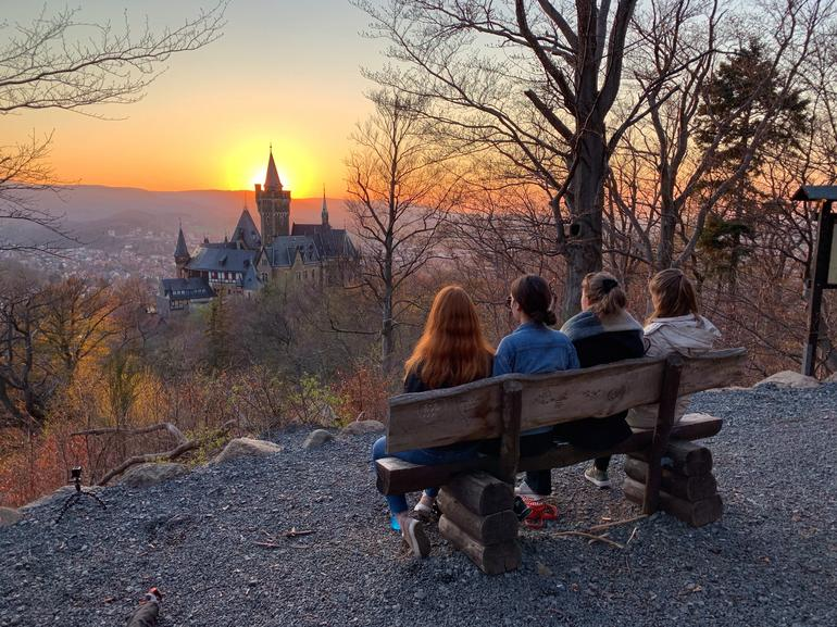 Outgoing exchange students sitting on a bench watching the sunset behind a castle in Germany