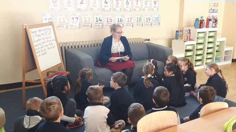 Female student reading for children in a school
