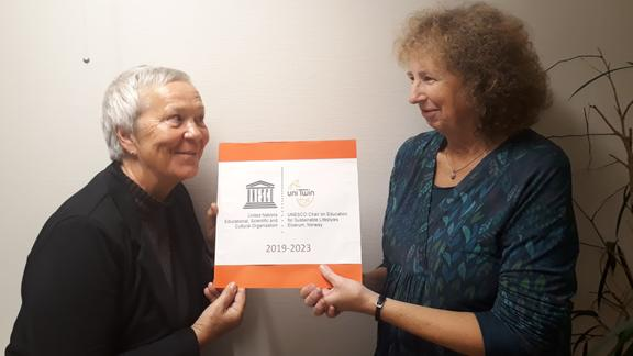 Rector Kathrine Skretting and UNESCO Chair holder Victoria W. Thoresen are standing opposite each other holding a plaque between them with UNESCO Chair logo.