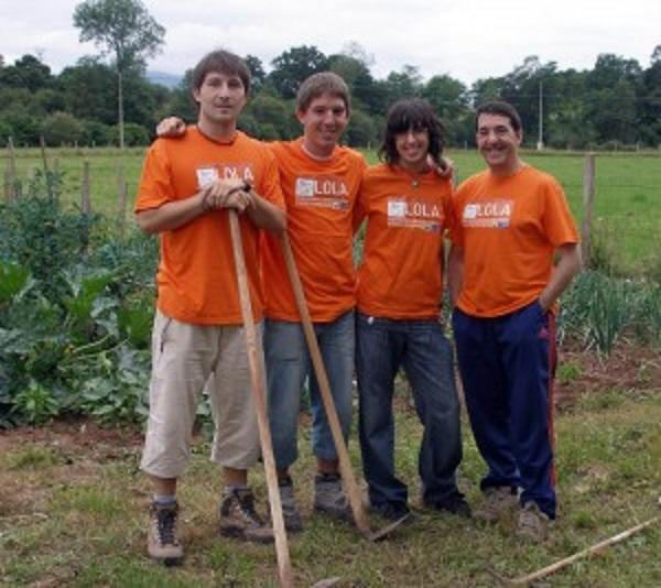 Four students standing outside in a vegetable garden holding garden utensils and wearing orange T-shirts with LOLA on.