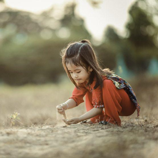 A little girl in colourful clothes playing with the soil during daytime
