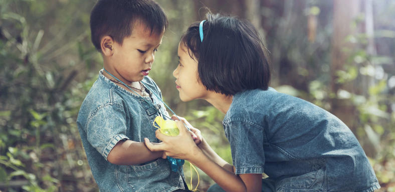 Little boy and older girl in denim blue clothing playing together outside